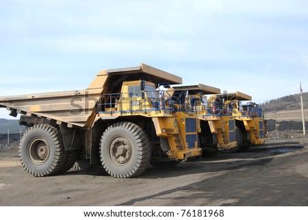 TUGNUI, RUSSIA - APRIL 2: Giant trucks are ready for coal transportation at the opening of Tugnuiskaya coal-preparation plant on April, 2, 2008 in Tugnui, Buryatia, Russia. - stock photo