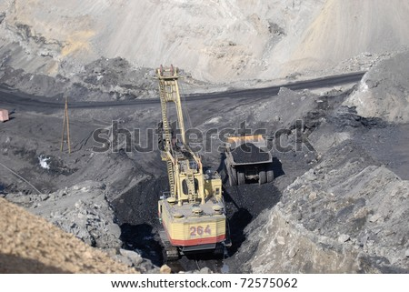 TUGNUI, RUSSIA - APRIL 2: The opening of Tugnuiskaya coal-preparation plant.  A mining shovel puts coal into a hauler, April, 2, 2008 in Tugnui, Buryatia, Russia. - stock photo