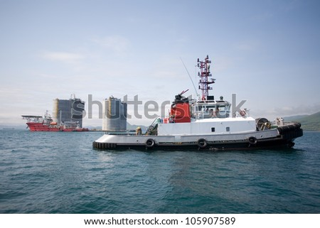Tugs at the base of offshore oil drilling platform. Sea Japan. Russian coast. - stock photo