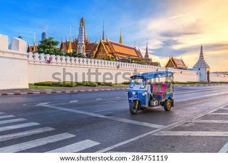Tuk Tuk is parking in front of Wat Phra Kaeo or Grand Palace, Bangkok, Thailand. This is a beautiful scene of the palace with the twilight sky. - stock photo