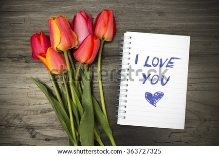 "tulip bouquet and notepad with words ""I love you"" - stock photo"
