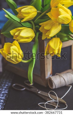 Tulip flower arrangement in a wooden container with old antique scissors and spool of thread