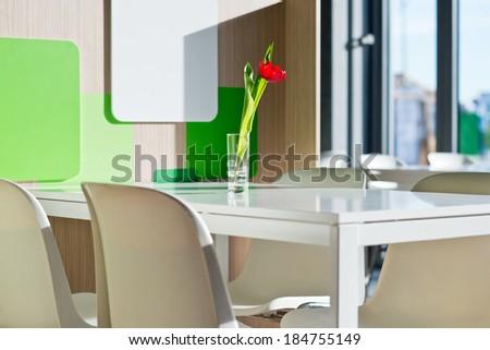 Tulip in the vase in empty public food court - stock photo