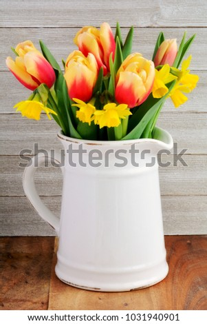 Tulips and daffodils in vintage jub on rustic wooden background.  In vertical format and shot in natural light.