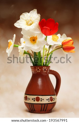 Tulips and narcissus in vase - stock photo