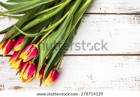 Tulips arrangement on aged wood planks background for wedding invitation, greetings card, birthday and invitations card - stock photo