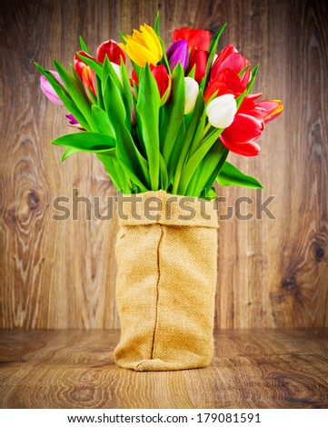 Tulips flowers in the sack on wooden background - stock photo