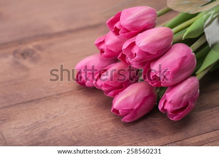 Tulips flowers on wooden table - stock photo