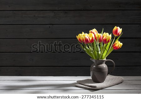 Tulips in vase, wooden background