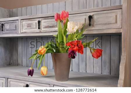 Tulips on an old fashioned bookshelf in shabby chic,