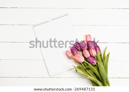 Tulips with blank card on white wooden background  - stock photo