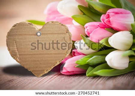 tulips with empty message cardboard for own message - stock photo