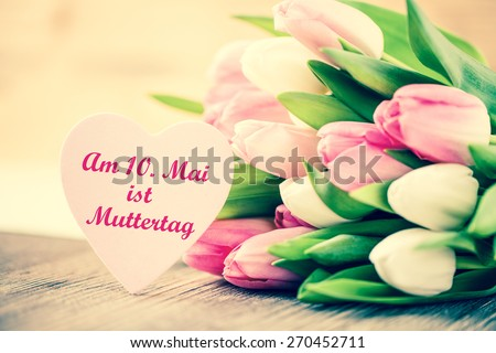 """tulips with message saying """"On the 10th of May is Mother's Day"""" in German - stock photo"""