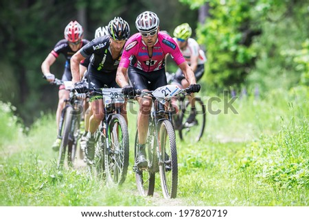 TULLINGE, STOCKHOLM - JUNE 8: Group of elite mountain bikers cycling uphill at Lida loop race 2014 during a sunny day in the Swedish nature. June 8, 2014 in Stockholm, Sweden.