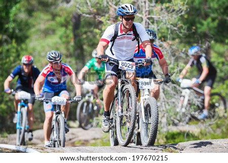 TULLINGE, STOCKHOLM - JUNE 8: Group of mountain bike cyclists thru a rocky section in the forest at Lida loop race 2014 during a sunny day in the Swedish nature. June 8, 2014 in Stockholm, Sweden.