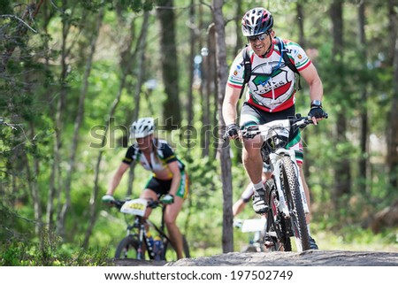 TULLINGE, STOCKHOLM - JUNE 8: Two cyclists in the forest during Lida loop race 2014 during a sunny day in the Swedish nature. June 8, 2014 in Stockholm, Sweden.