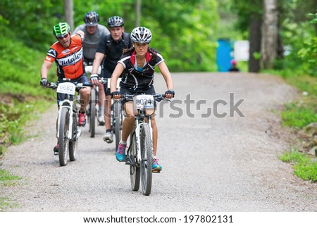 TULLINGE, STOCKHOLM - JUNE 8: Woman leads a group at mountain bike on a gravel road at Lida loop race 2014 during a sunny day in the Swedish nature. June 8, 2014 in Stockholm, Sweden.