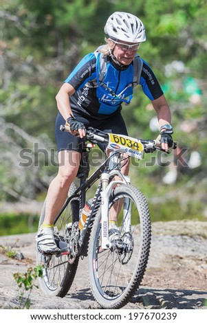 TULLINGE, STOCKHOLM - JUNE 8: Woman on mountain bike out of a curve in rocky part of the forest at Lida loop race 2014 during a sunny day in the Swedish nature. June 8, 2014 in Stockholm, Sweden.