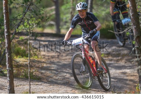 TULLINGE, SWEDEN - JUNE 12, 2016: MTB cyclist taking a curve in the forests at Lida loop during summer. One of swedens biggest mountainbike races. - stock photo