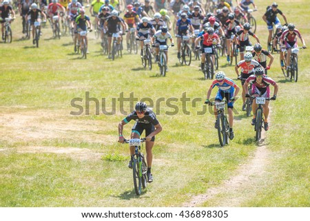 TULLINGE, SWEDEN - JUNE 12, 2016: Start of a large group of MTB cyclists going uphill at Lida loop during summer. One of swedens biggest mountainbike races. - stock photo