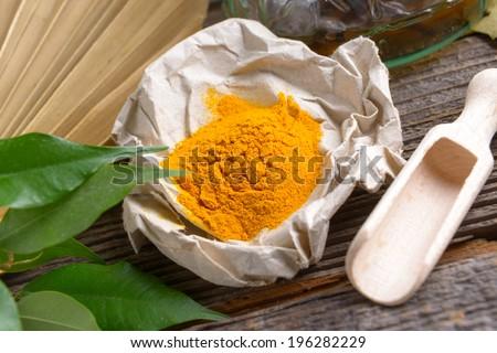 Tumeric powder spice on wooden board  - stock photo