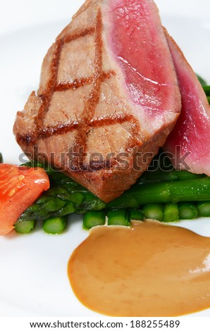 Tuna a grill with an asparagus close-up - stock photo