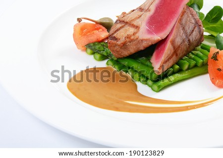 Tuna a grill with an asparagus close-up