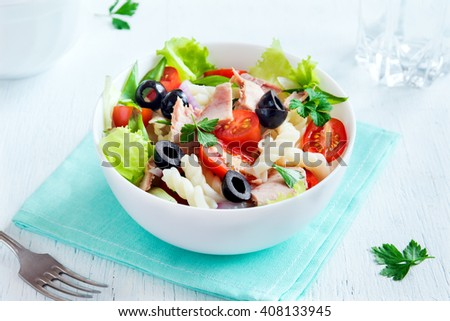 Tuna and pasta salad with fresh tomatoes, olives, herbs close up - stock photo