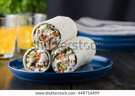 Tuna burritos with avocado tomato and mayonnaise on rustic background - stock photo
