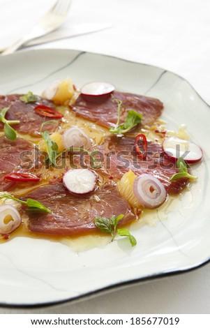 Tuna carpaccio with radish, onion and olive oil on a white plate - stock photo