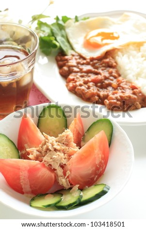 Tuna fish and tomato salad with curry rice on background