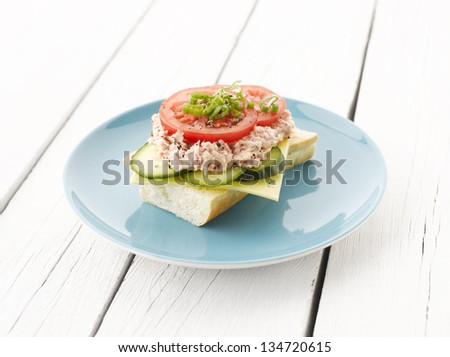 Tuna Fish Salad Sandwich with Caper, Cucumber, Cheese, Lettuce and Tomato on White Wooden Table. Shallow focus. - stock photo