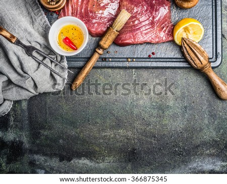 Tuna fish steaks with lemon, oil and spices on rustic background, top view, place for text - stock photo