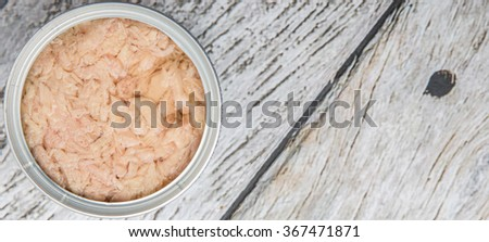Tuna flakes in tin can over wooden background - stock photo