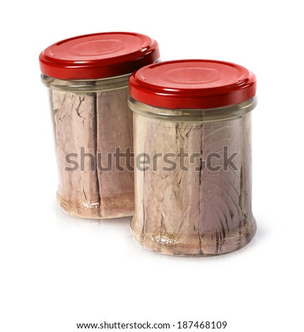 tuna in olive oil packed in glass jars with shadows and reflections on white. - stock photo