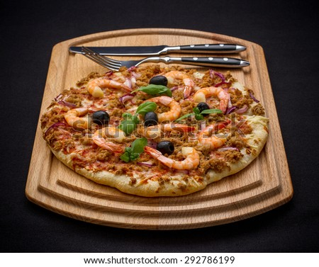 Tuna pizza with shrimp and cutlery, close up - stock photo