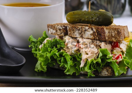 Tuna salad sandwich with lettuce on rye toast with butternut squash soup, potato chips, and a pickle - stock photo
