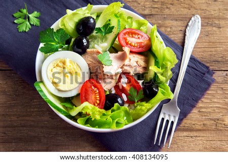 Tuna salad with egg, tomatoes, black olives, rice and greens close up - stock photo