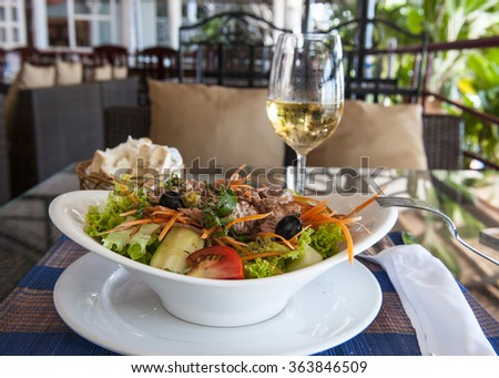 tuna salad with glass of white wine on the table in restaurant