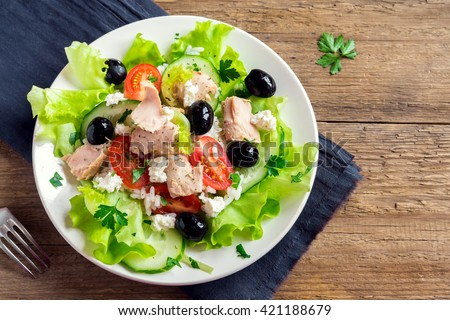 Tuna salad with tomatoes, black olives, rice, feta cheesse and greens on rustic wooden background with copy space - stock photo