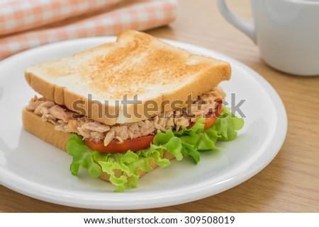 Tuna sandwich on plate and coffee cup - stock photo