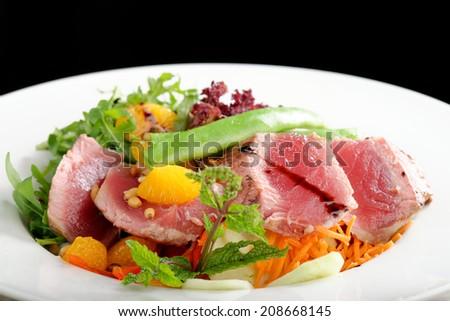 Tuna Sashimi - Maguro (fresh raw tuna) on Daikon (White Radish). Garnished with Ginger, Wasabi, Seaweed, Cucumber, Salad Leaf and Lemon  - stock photo