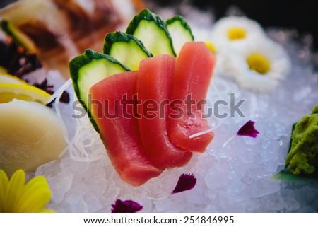 Tuna Sashimi - Maguro fresh raw tuna on Daikon White Radish. Garnished with Ginger, Wasabi, Seaweed, Cucumber, Salad Leaf and Lemon - stock photo