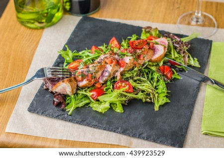Tuna steak and a glass of wine - a delicious and healthy dinner. Fish close up on a decorated table in the restaurant .  - stock photo