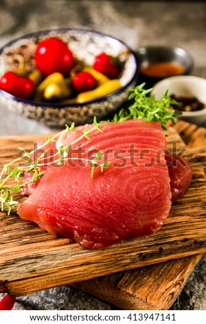 Tuna steak on a wooden board with pepper and cucumber, tasty fish dinner - stock photo