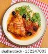 Tuna steak poached in tomato sauce. - stock photo