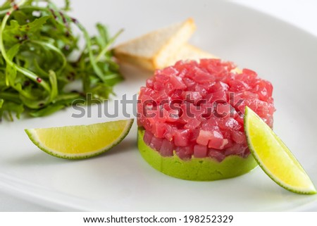 Tuna tartar garnished with lime and arugula isolated on white background - stock photo