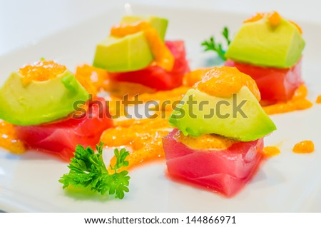 Tuna with avocado on top in white dish