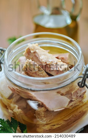 Tuna with parsley  in a glass jar on wooden table - stock photo