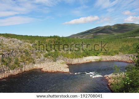 Tundra Landscape with trees, river and hills in northern Norway